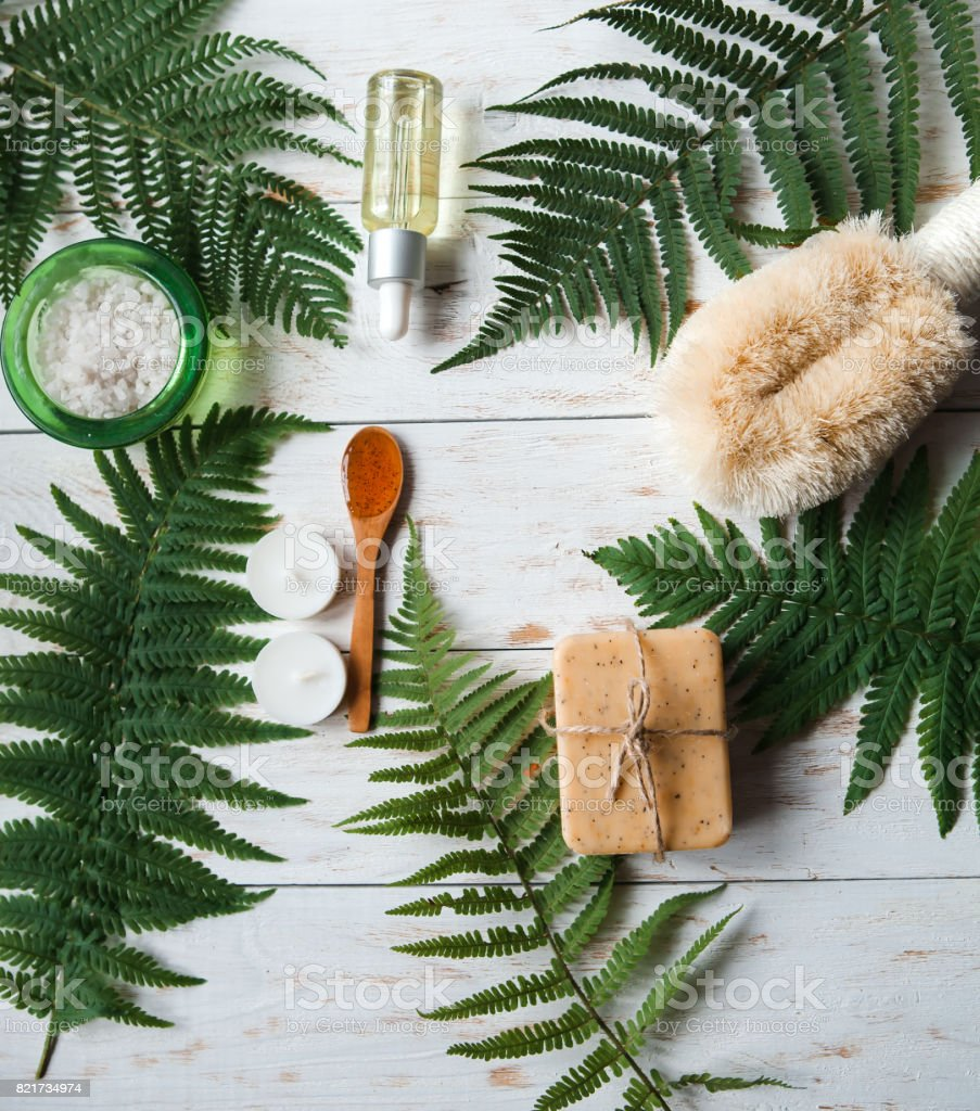 skin care and body scrub with natural ingredients, salt, natural lotion,Washcloth and soap set up on white wooden background. flat lay stock photo