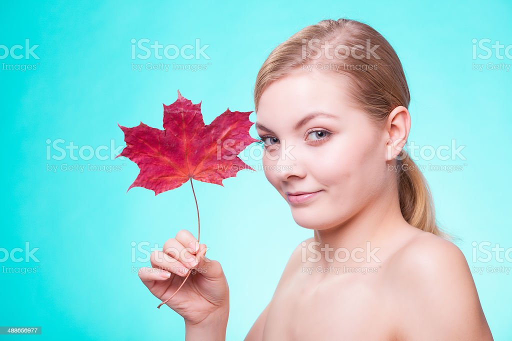Skin care. Portrait of young woman girl with red leaf. royalty-free stock photo