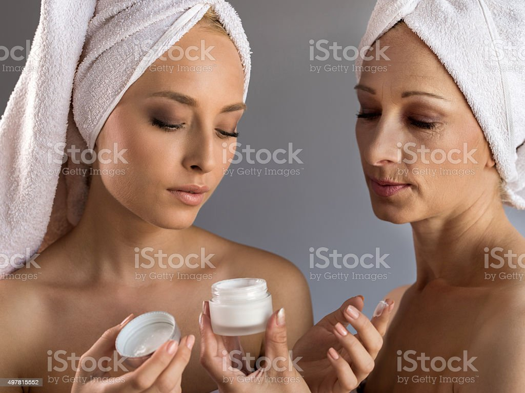 Skin care with moisturizer among mother and daughter. stock photo