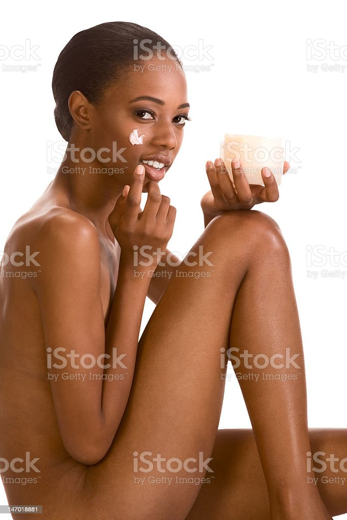 Skincare - Naked Afro American girl putting cream on face royalty-free stock photo