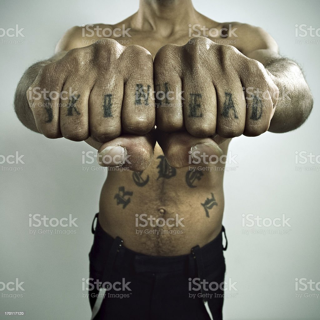 Skinhead Showing off Knuckle tattoo stock photo