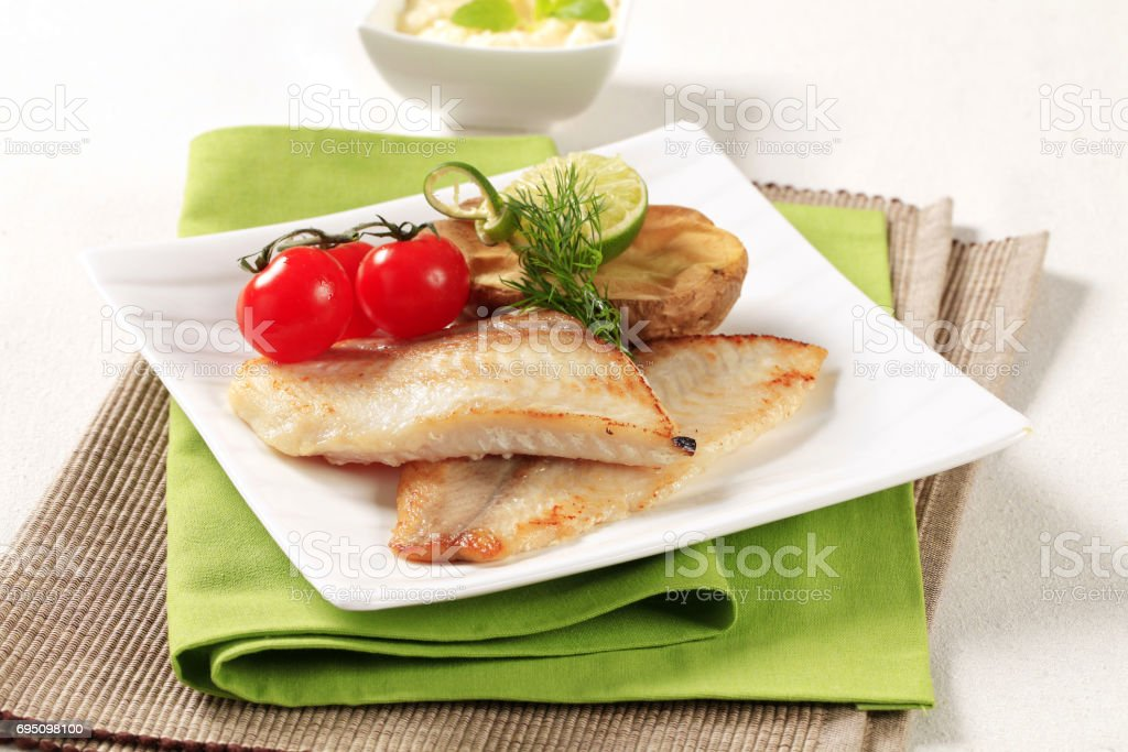 Skinless fish fillets with baked potato half stock photo