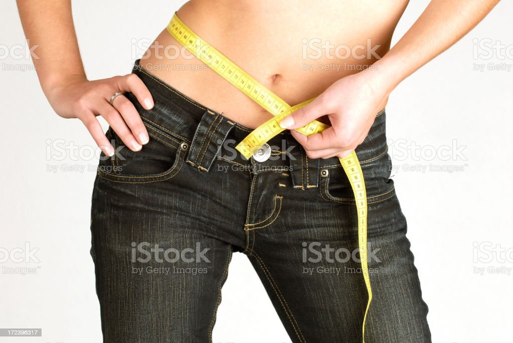 Skinny female measuring her stomach royalty-free stock photo