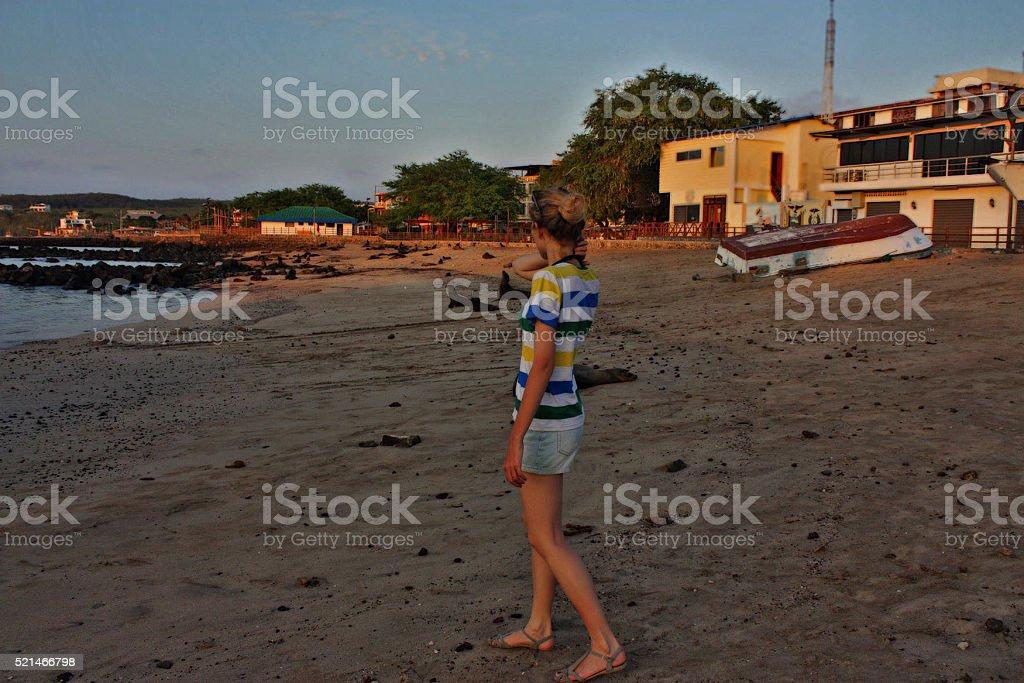 skinny girl near Fur seals at beach, Galapagos islands (Ecuador) stock photo
