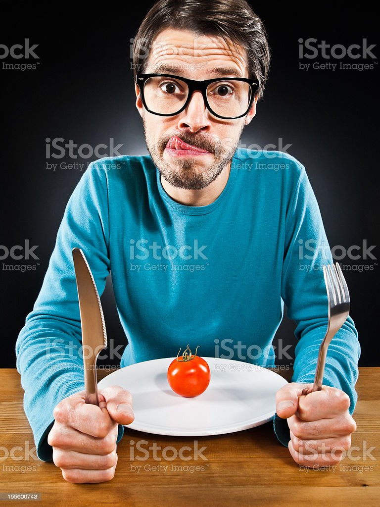 Skinny, hungry man with cherry tomato on plate, humorously stock photo