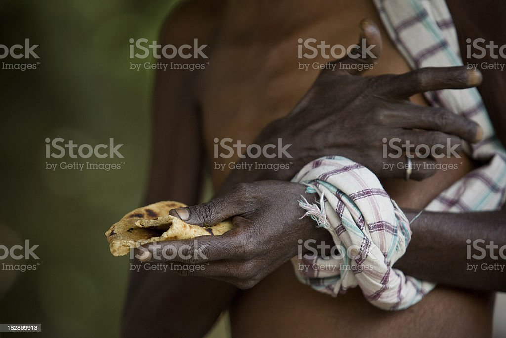 Skinny senior Indian man eating bread stock photo