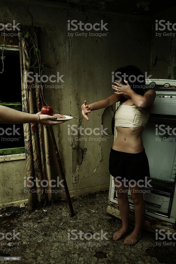 Skinny Teen Girl Refusing Food in Trashy House royalty-free stock photo