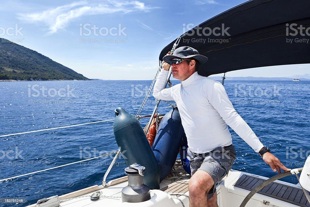 Skipper driving sailboat royalty-free stock photo