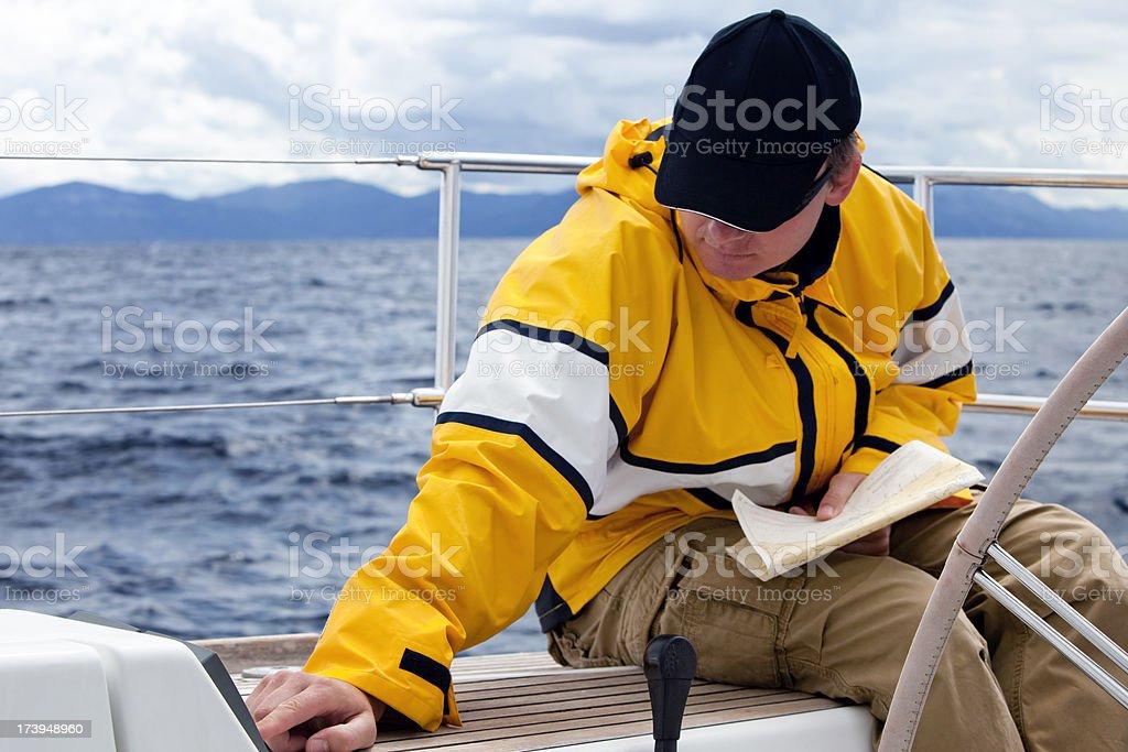 Skipper navigating sailboat royalty-free stock photo