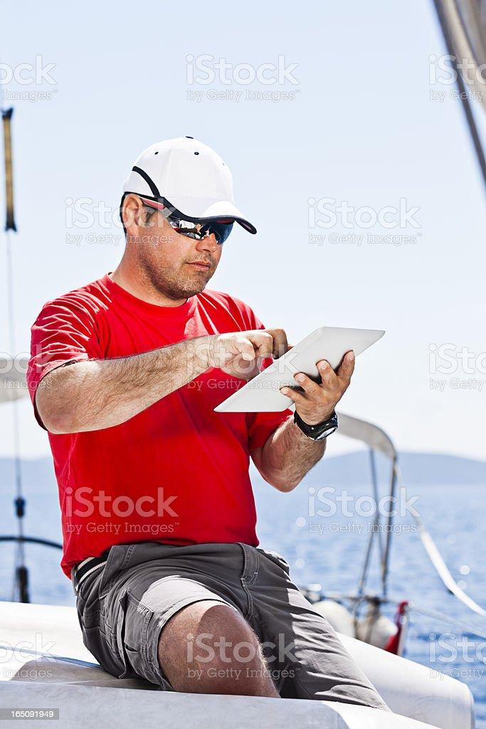 Skipper using digital tablet on sailboat stock photo