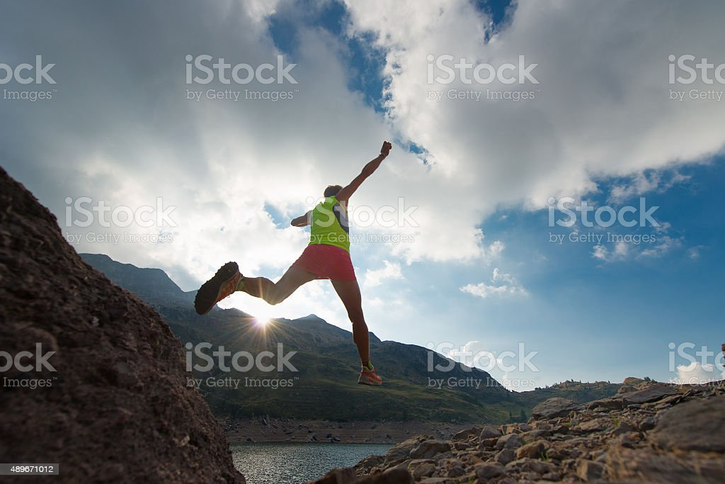 Skipping girl as he runs in the mountains stock photo