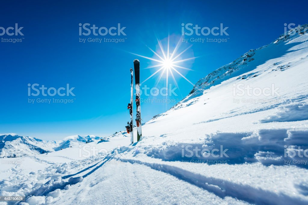 Skis and ski poles on remote slope stock photo