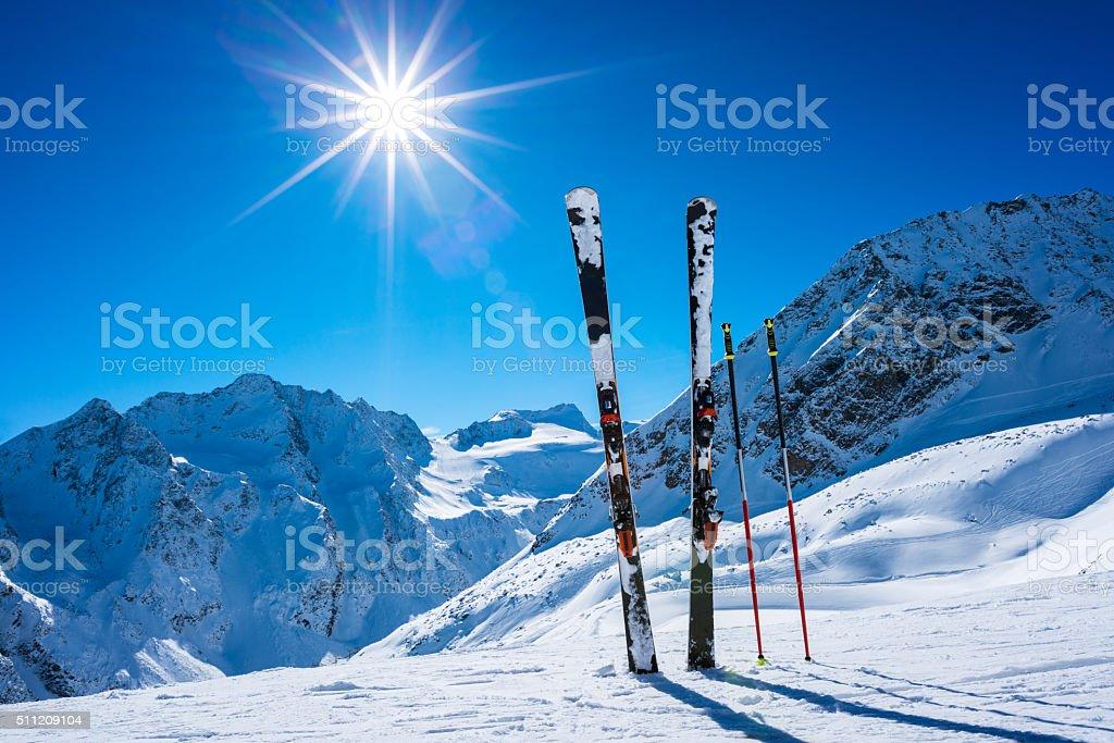 Skis and ski poles on top of ski resort stock photo