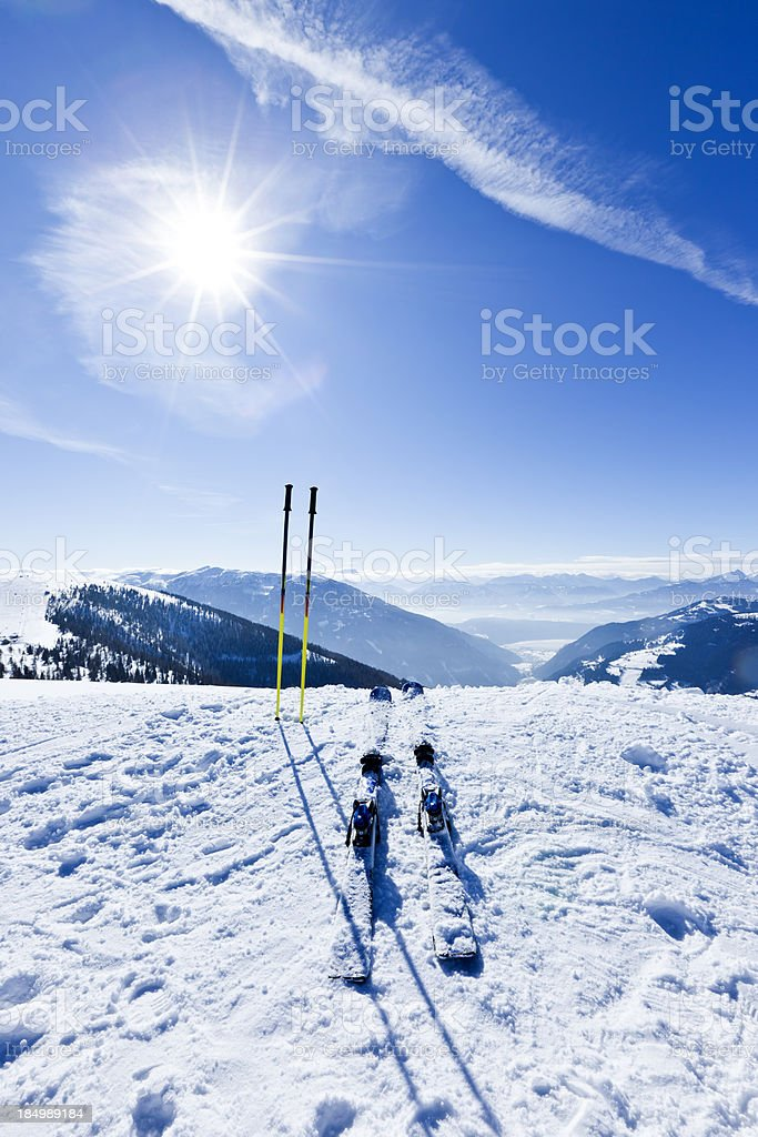 Skis and ski poles on top of slope stock photo