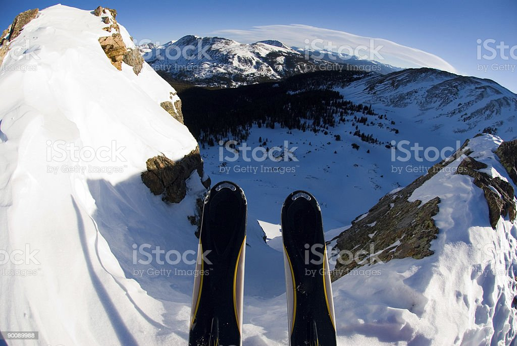 Skis Dropping Into Extreme Backcountry Mountain Terrain stock photo