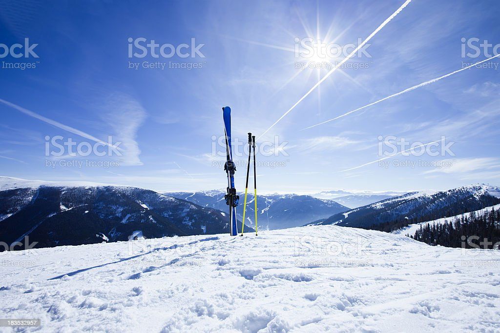 Skis on top of slope against sun stock photo
