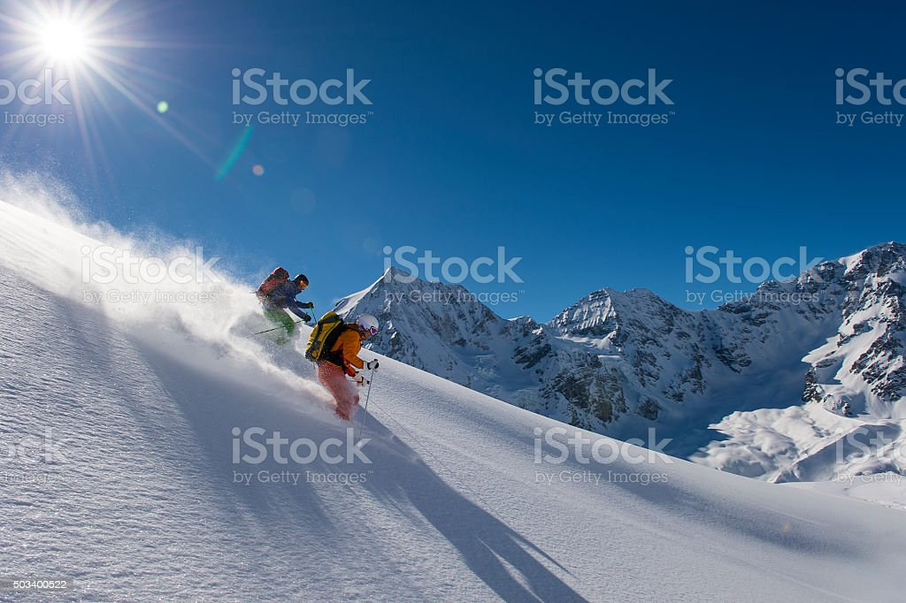 skitouring downhill - powder skiing stock photo