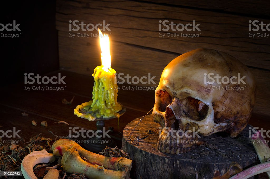 Skull and light candle  - Still life style stock photo
