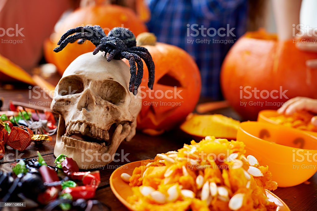Skull, candies, pumpkin pulp and Jack O'lanterns on the table stock photo