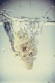 Skull drop into water with splash