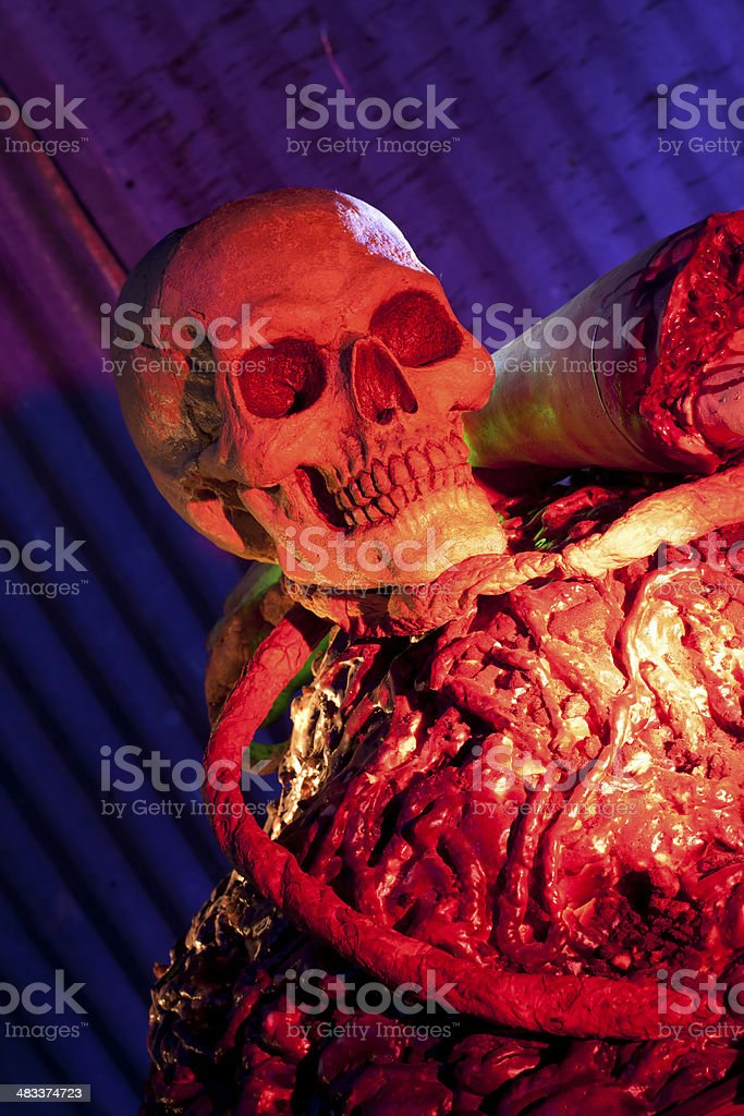 Skull on a pile of fake guys and body parts stock photo
