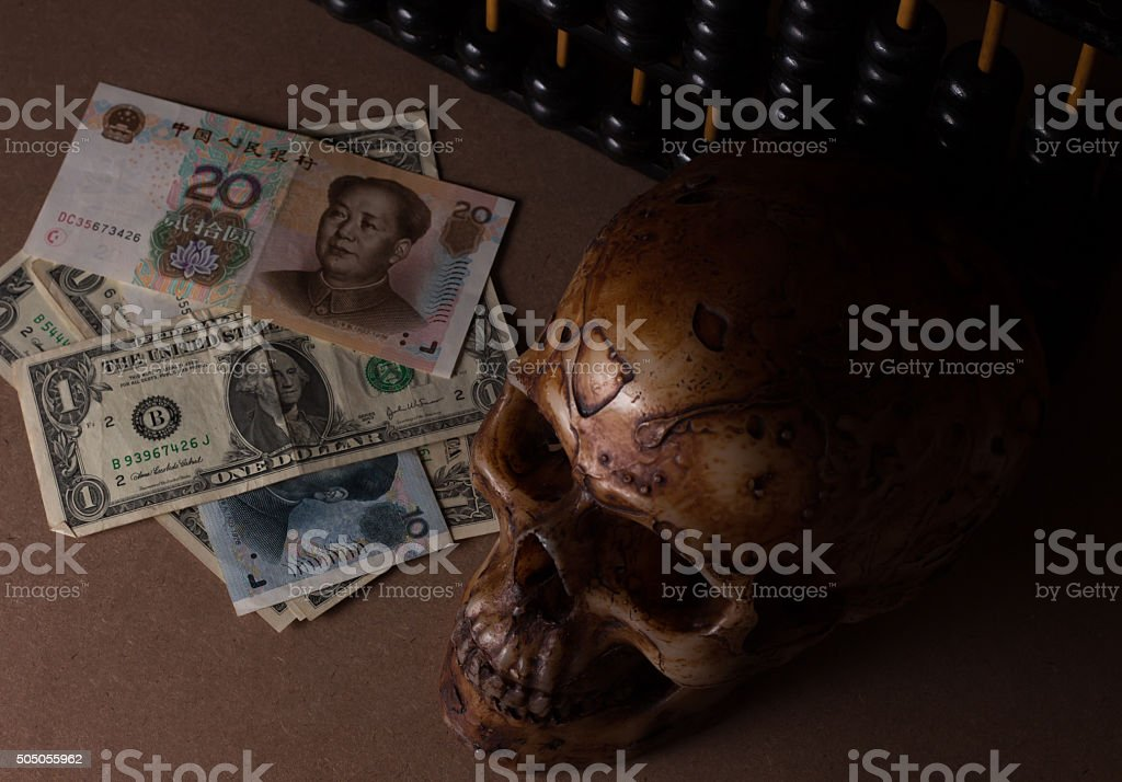 skull on old wood with banknote yuan and dollar stock photo