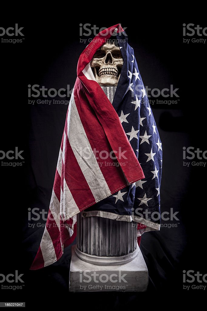 Skull on Pedestal Wrapped in American Flag, Black Background royalty-free stock photo