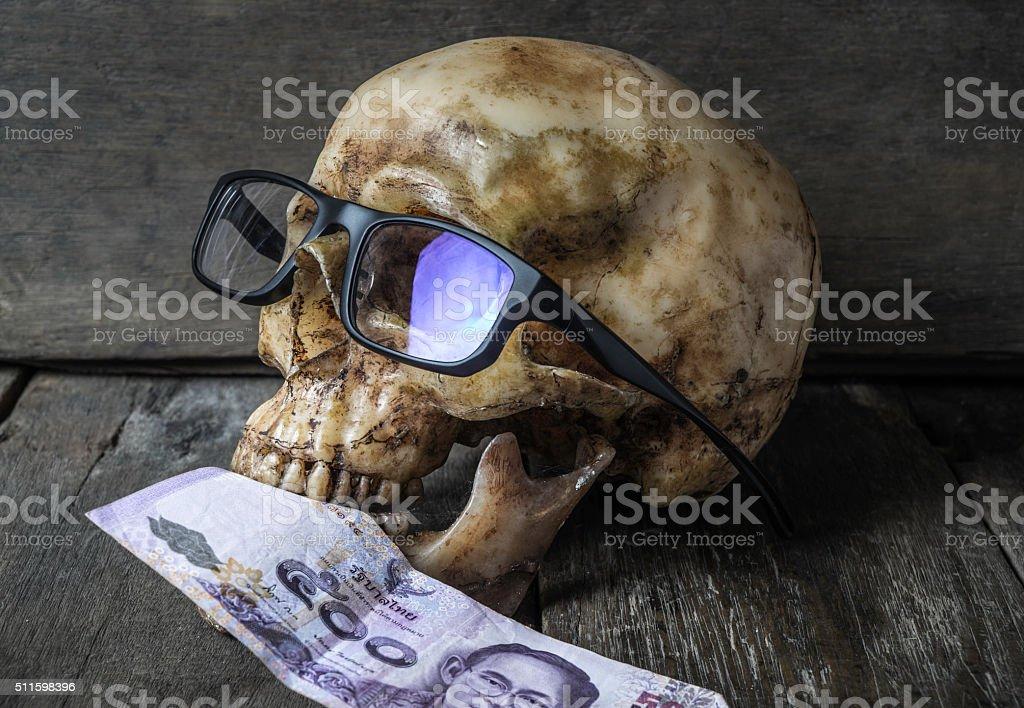 Skull wearing Glases Eating Money stock photo