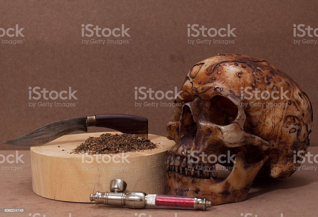 skull with marijuana drug still-lift concept dark tone stock photo