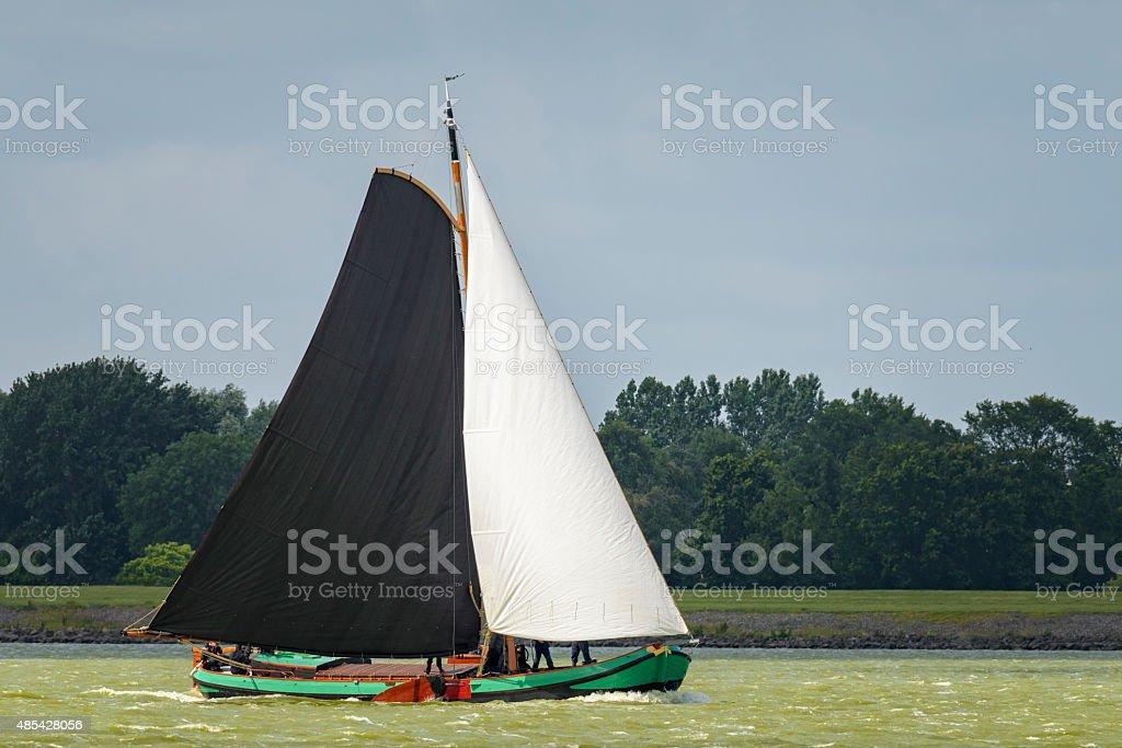 Skutsje classic sailboat sailing on a lake in the sun stock photo