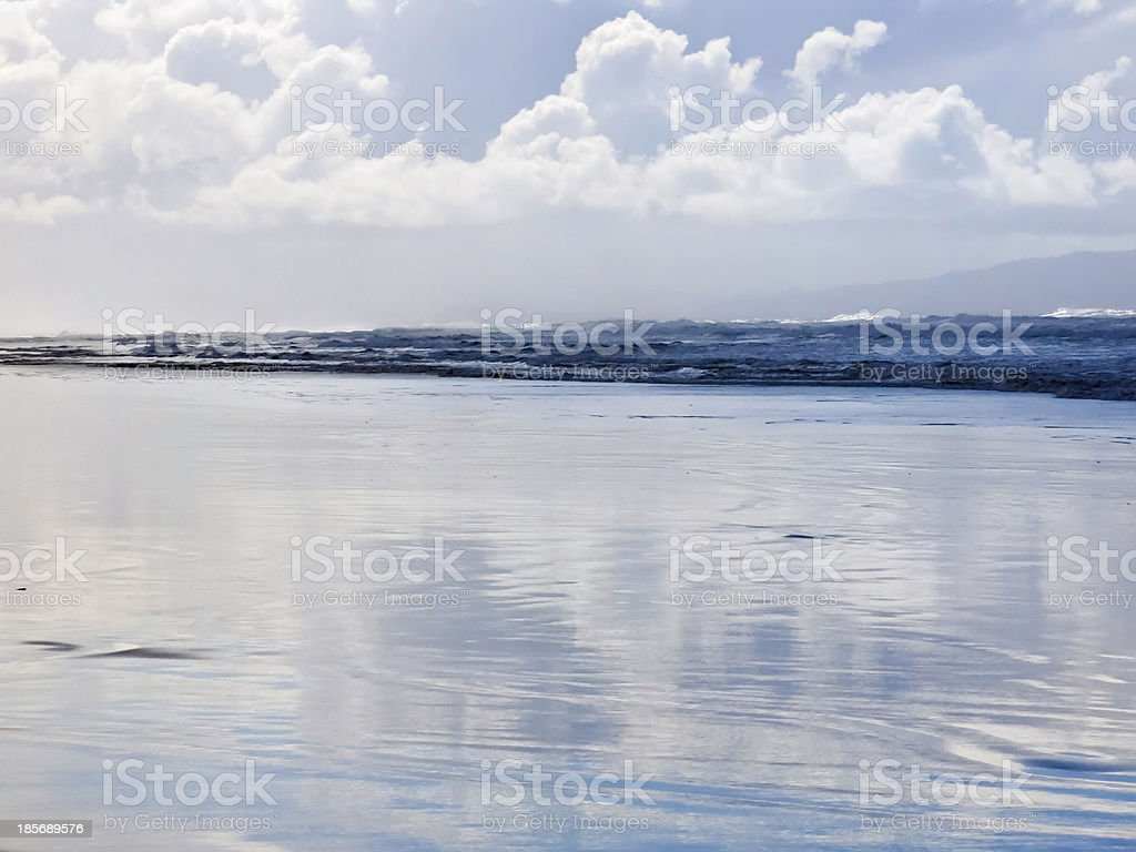 Sky on wet beach with incoming waves stock photo