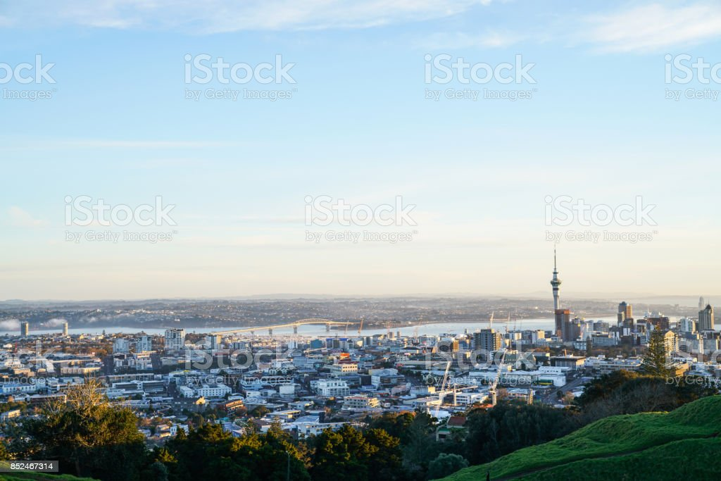 Sky Tower and Auckland Harbour Bridge landmarks on city skyline from atop Mount Eden. stock photo