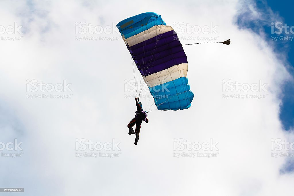 Skydiver and colorful parachute stock photo