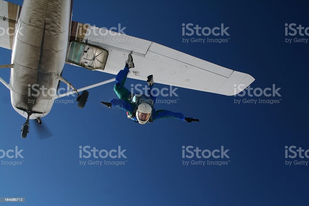Skydiver exiting a small airplane stock photo