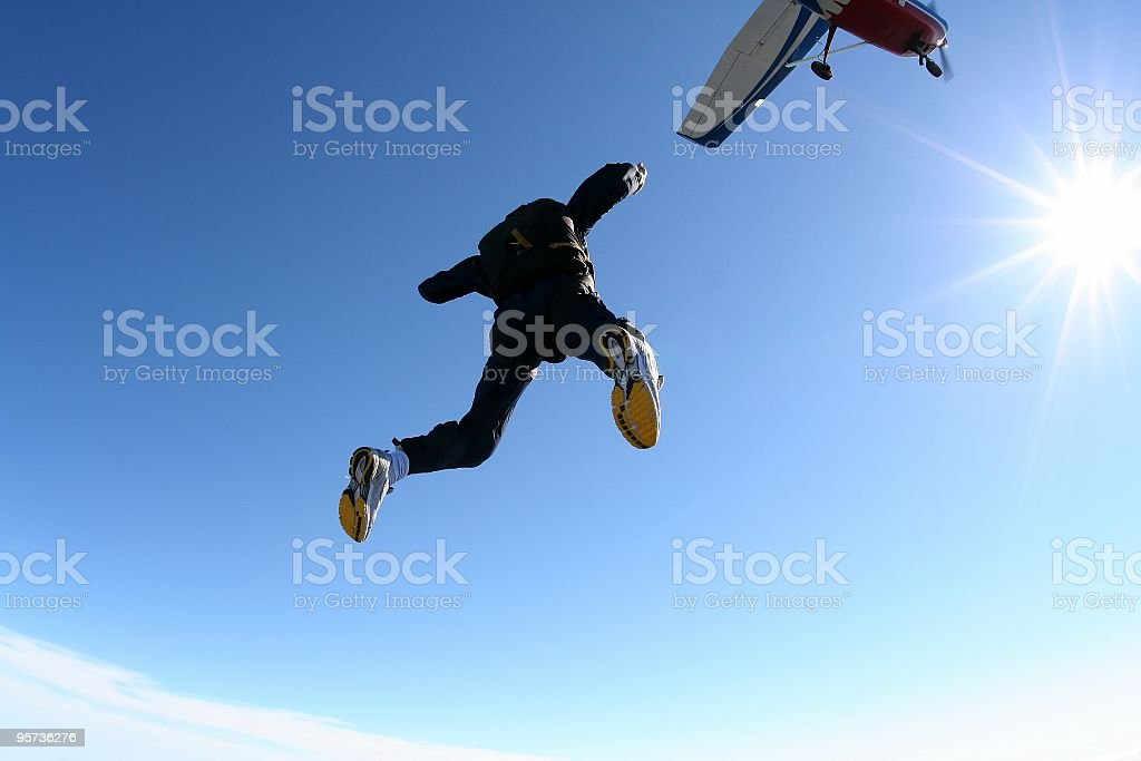 Skydiver exiting an airplane stock photo