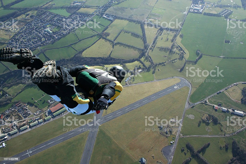 Skydiver free falling above countryside stock photo