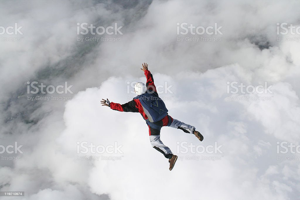 Skydiver in freefall with clouds beneath him royalty-free stock photo