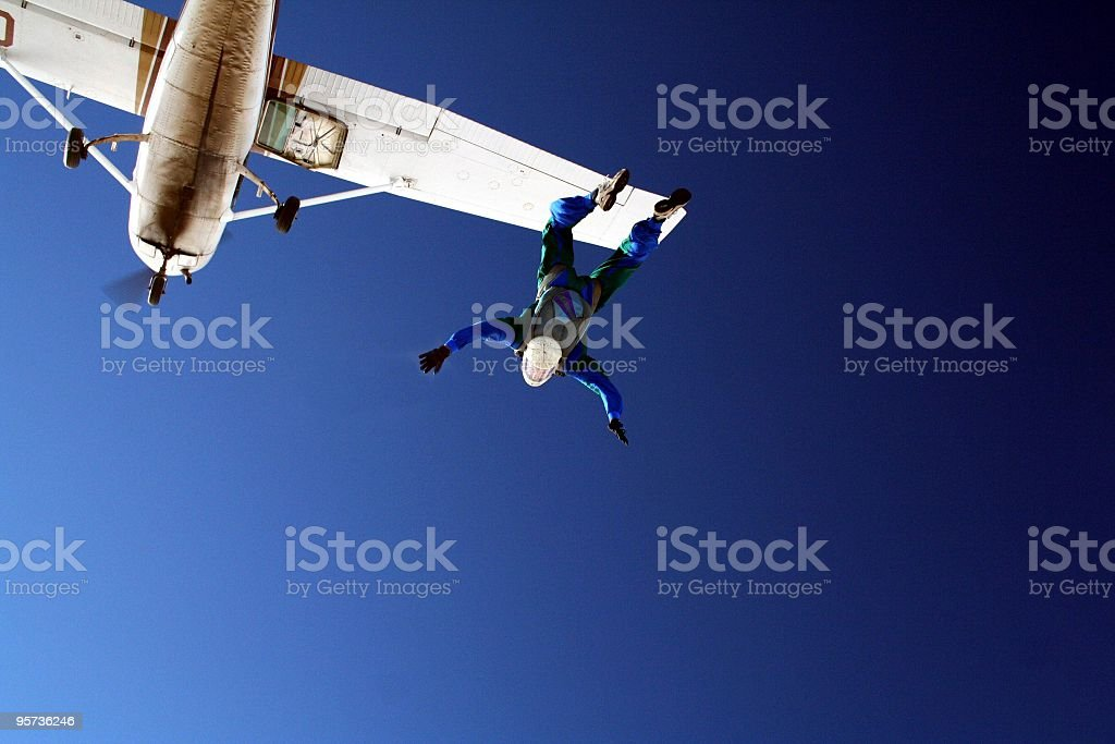 Skydiver jumping out of white airplane on clear blue sky stock photo