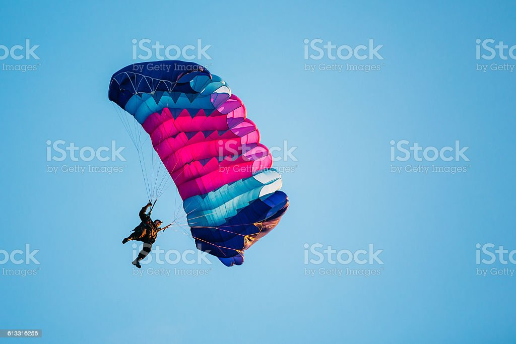 Skydiver On Colorful Parachute In Blue Clear Sky stock photo