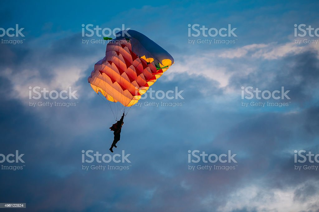 Skydiver On Colorful Parachute In Sky stock photo