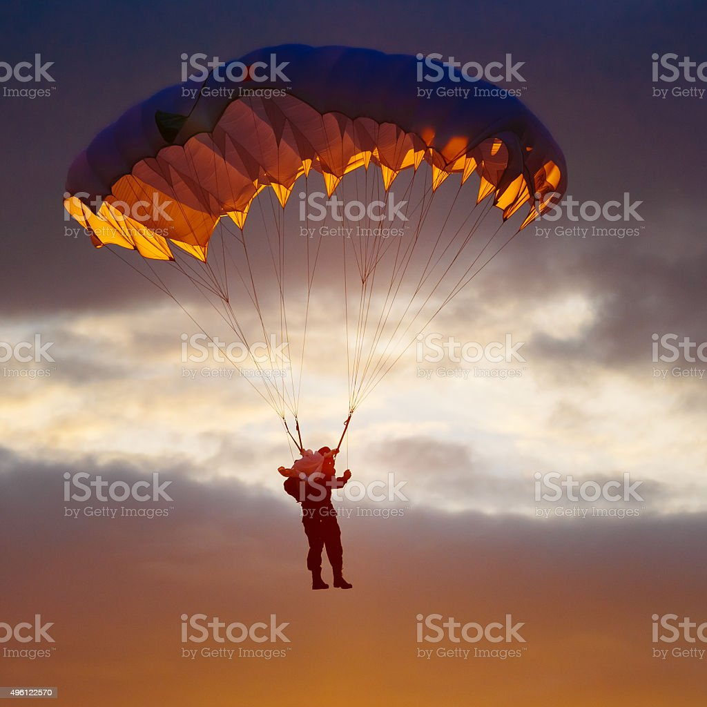 Skydiver On Colorful Parachute In Sunny Sky stock photo