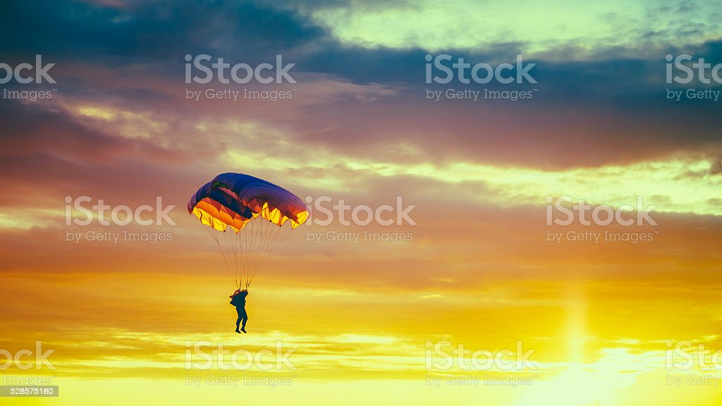 Skydiver On Colorful Parachute In Sunny Sunset Sunrise Sky stock photo