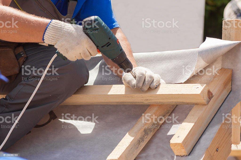 Skylight installation. Roofer builder worker use skrewdriver stock photo