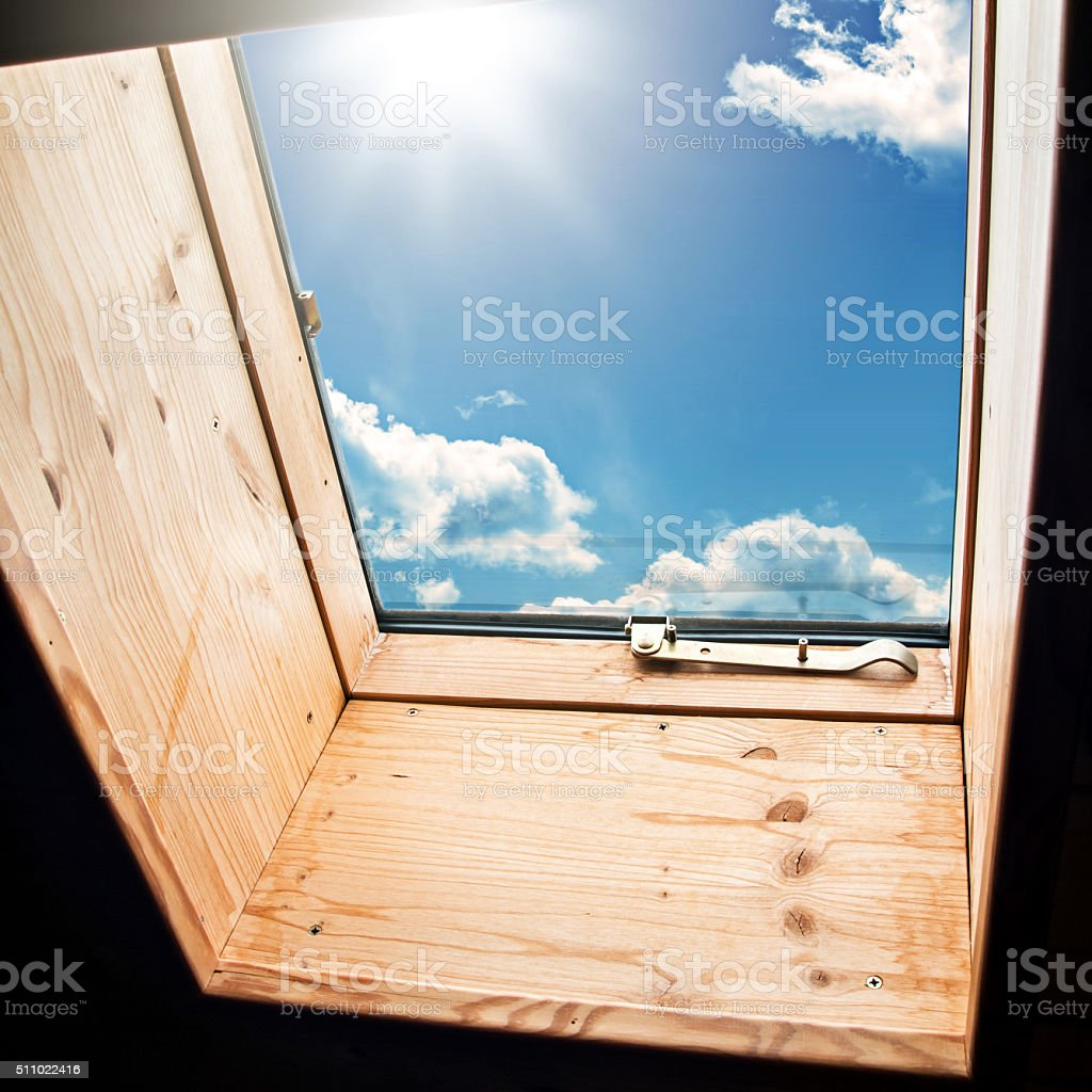 Skylight window close-up in wooden attic with sunny sky outside stock photo