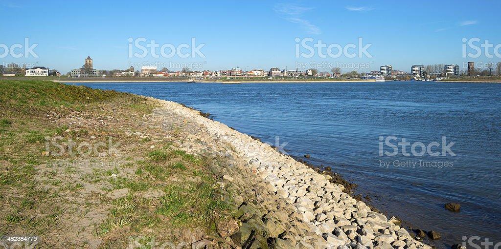 Skyline of a village along a sunny river stock photo