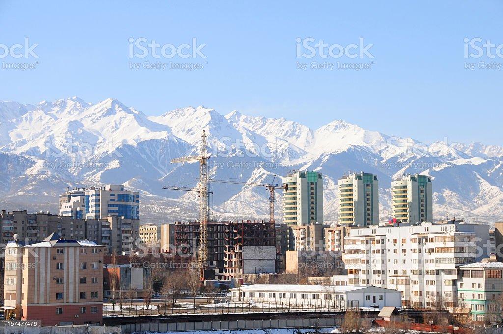 Skyline of Almaty city and snowy mountains stock photo