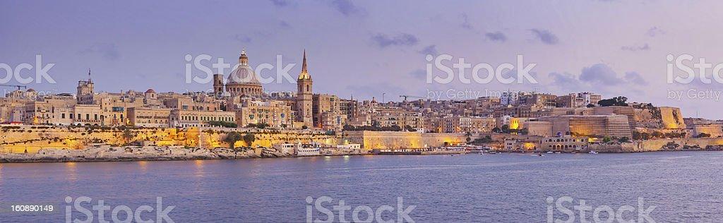 Skyline of Malta seen from the ocean at dusk stock photo