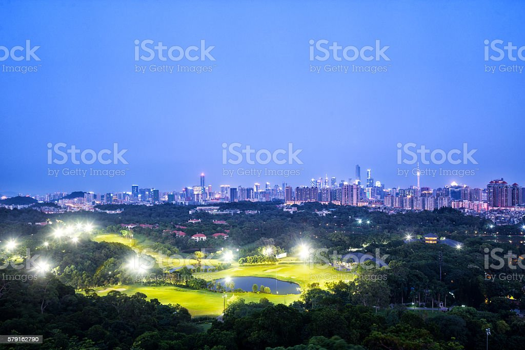 skyline of modern city with golf course at night stock photo
