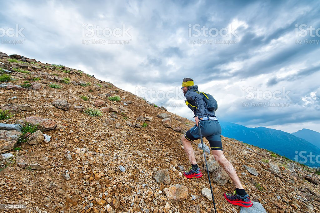 Skyrunner athlete while training in the mountains with sticks stock photo