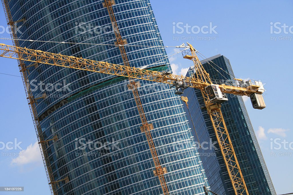 A skyscraper being constructed by a derrick stock photo